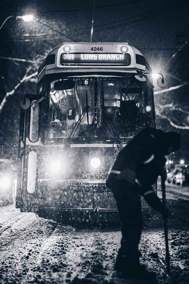 train in snow with a person clearing the tracks