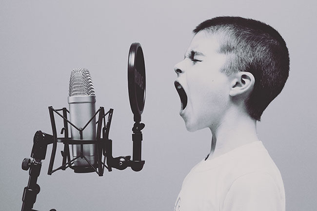 Boy shouting into a microphone, black and white