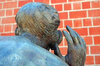 picture of a sculpture, focused on back of head with hand to ear.