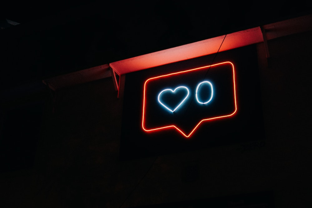 neon sign of a dialog box with a heart and the number zero inside